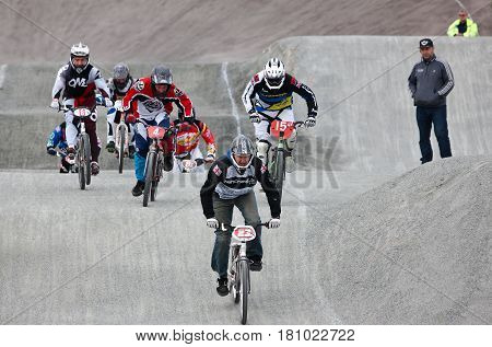 GRAVESEND, UK - APRIL 12: Riders competing in the mens class of the UK National BMX championships at the Kent cyclopark head over the rollers section at speed on April 12, 2014 in Gravesend