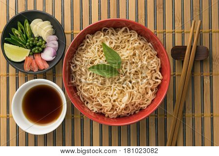 noodles with sauce or shoyu and ingredient on wood/bamboo backgroound top view