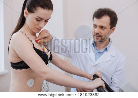 Healthy cardio. Distinguished smart contemporary cardiologist connecting vires to several sensors on womans chest while testing modern equipment for indicating cardiac diseases