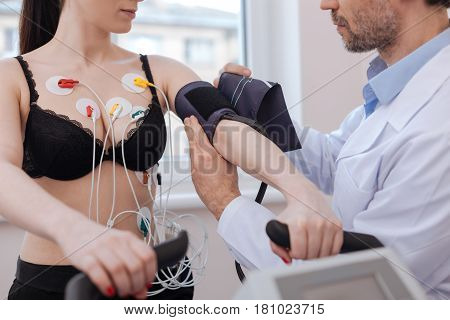 Checking all indicators. Qualified attentive pleasant man using several devices for testing his patients cardiovascular system while making her doing exercises
