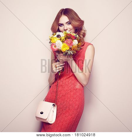 Blonde young woman in elegant red dress. Girl posing on a beige background with handbag. Jewelry and hairstyle. Lady with spring bouquet of flowers. Fashion photo