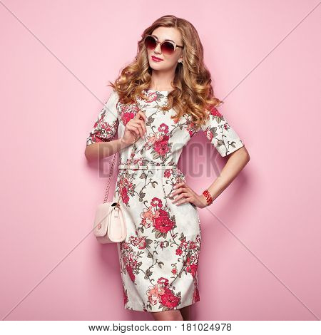 Blonde young woman in floral spring summer dress. Girl posing on a pink background. Summer floral outfit. Stylish wavy hairstyle. Fashion photo. Glamour lady in sunglasses with handbag