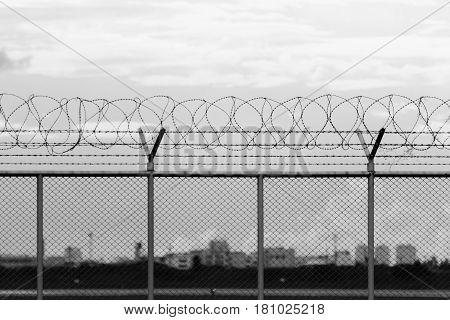 security restricted area with a barbed wire fence black and white photo