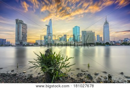 Ho Chi Minh City, Vietnam - March 25th, 2017: Riverside City sunset clouds in the sky at end of day brighter coal sparkling skyscrapers along beautiful river in Ho Chi Minh City, Vietnam