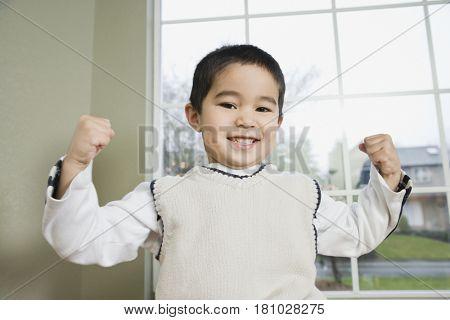 Mixed Race boy flexing muscles