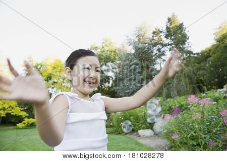 Mixed Race girl playing with bubbles