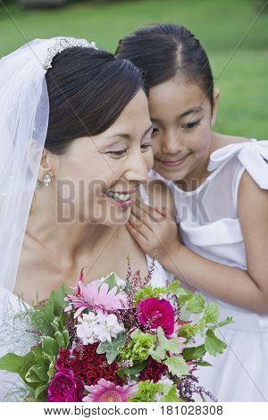 Asian bride and flower girl hugging