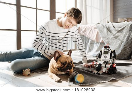 Good mood. Attractive boy putting left hand near robot patting his home pet while bowing his head