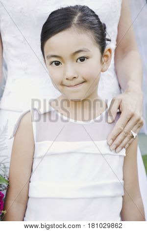 Mixed Race girl standing in front of bride