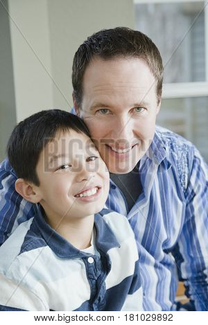 Mixed Race father and son hugging
