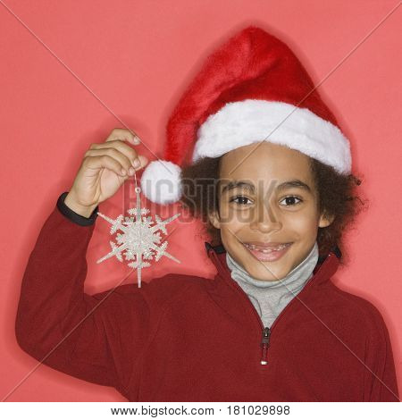 Mixed Race boy holding Christmas ornament