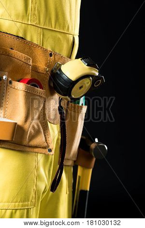 Close-up partial view of workman in tool belt on black