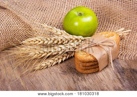 A stack of homemade cereal biscuits an apple and spikelets of wheat. Useful organic food.
