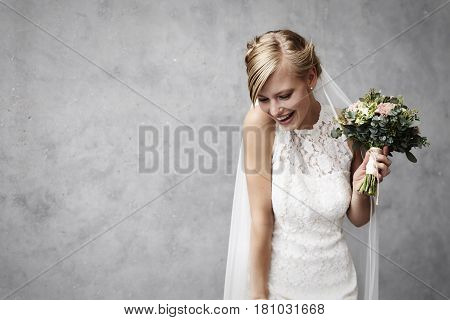 Joyous young bride holding flowers in studio