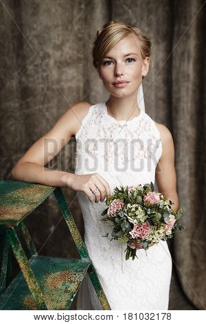 Young blonde Bride holding flowers portrait studio