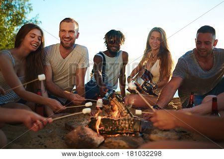 Teenage friends roasting marshmallows on campfire