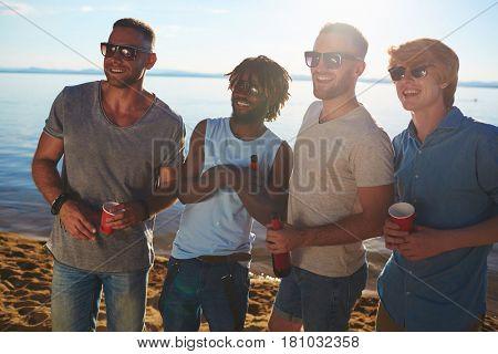 Multi-ethnic group of guys in sunglasses enjoying beach party
