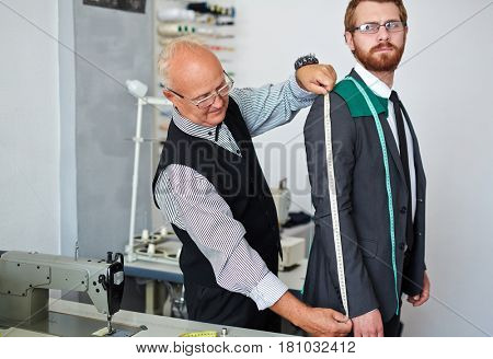 Tailor measuring sleeve of businessman jacket