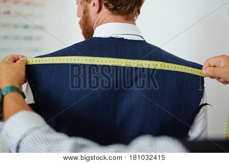 Clothier measuring back width of his client