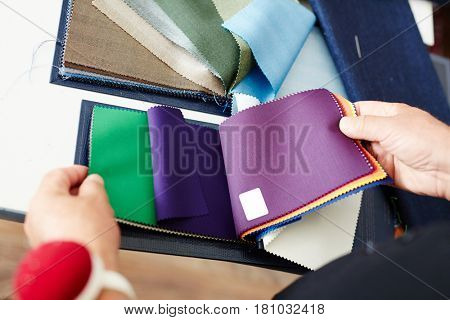 Tailor choosing textile and suitable color from samples