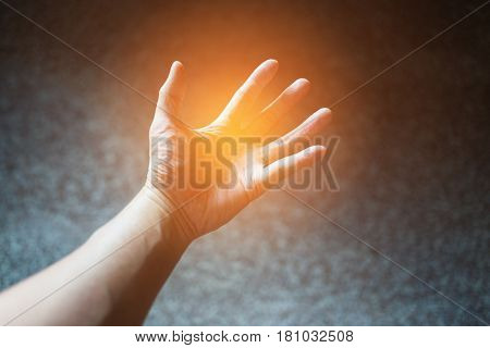 Abstract scene of powerful hand by soft orange light spreading on paw and fingers with blurry dark background.