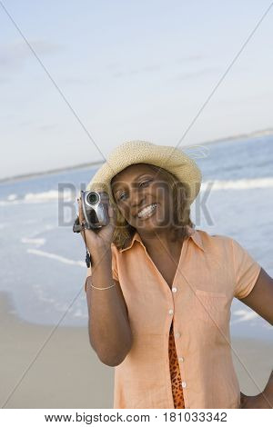 African woman holding video camera at beach