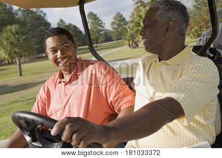 African father and adult son in golf cart