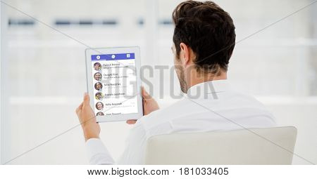 Digital composite of Rear view of businessman using social site on tablet PC
