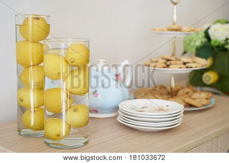 Tea table. tea time with chocolate chip cookies and lemons. Copy space with border. breakfast wooden table.