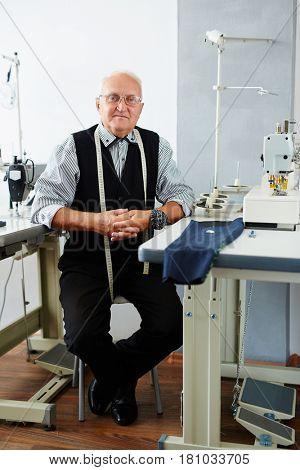 Mature tailor sitting by workplace in tailoring-shop