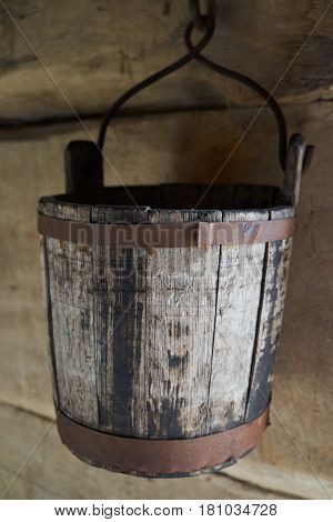 Old rustic Wooden bucket with handle on wooden background.