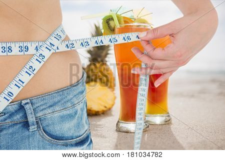 Digital composite of Midsection section of woman measuring waist with juices in background