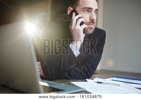 Portrait of modern bearded businessman working in office using laptop and talking by mobile phone against black background with lens flare
