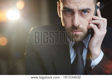 Portrait of modern businessman wearing black formal suit looking at camera while busy talking by mobile phone against black background with lens flare