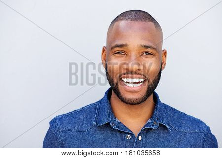 African American Man Laughing Against Gray Wall