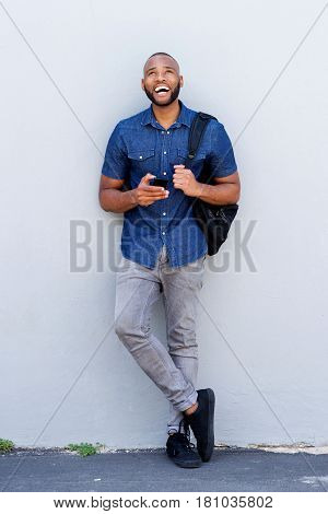 Cheerful Young African Man Standing With Mobile Phone