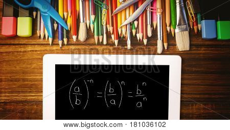 Digital composite of Overhead view of formula in digital tablet with color pencils and school supplies on wooden table