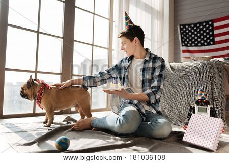 Look outside. Profile photo of positive boy sitting on the floor near his pet looking through the window, touching his dog