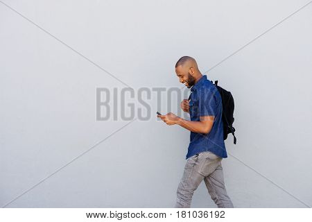 Happy Young Guy With Bag Walking With Mobile Phone
