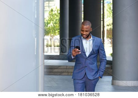 Young African Businessman Walking And Looking At Cellphone