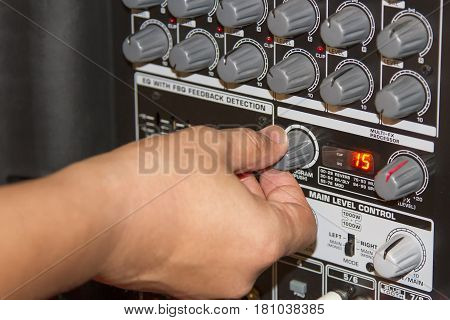 Hand adjusting volume sound of the mixer