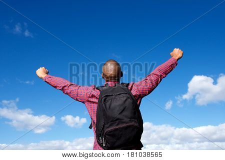 Guy With Backpack Standing Outdoors With Arms Outstretched