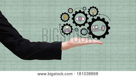 Digital composite of Digitally generated image of gears on hand against grid background
