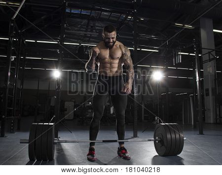The portrait of muscular athlete celebrating his succesfull attempt of deadlifting the barbell over his head.Functional training