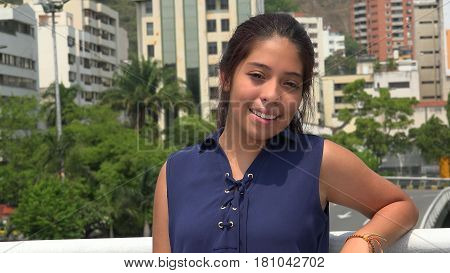 Hispanic Girl Smiling with Urban Buildings in Background