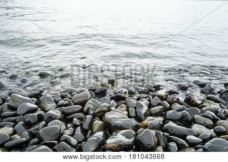 round stones at the seashore with sea waves