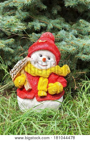Snowman toy on the grass under the spruce the celebration of Christmas in a warmer climate