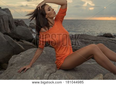 Sensual brunette woman in bright orange dress posing on the rocks over beautiful sea and sunset sky background