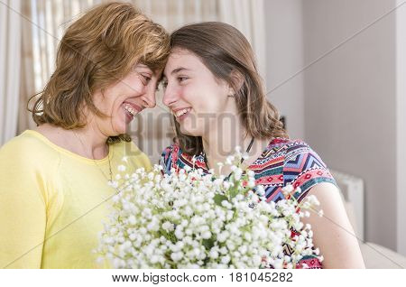 Woman And Child With A Bouquet Of Flowers In Their House. Mother's Day