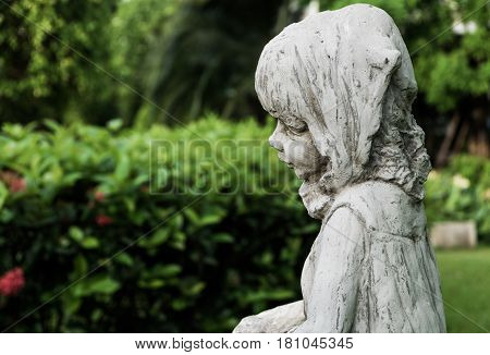 A white vintage little girl ceramic scupture in the garden selective focus.